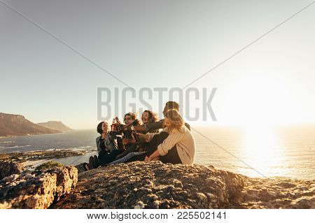 Group Of Friends Toasting Beers During Sunset