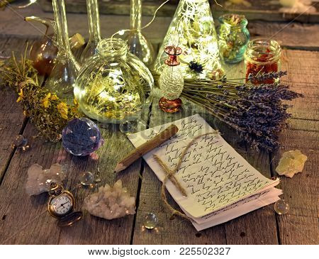 Witch Manuscript With Writings, Magic Bottles, Crystals And Lavender Flowers On Planks. Occult, Esot