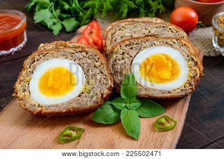 Meat Cutlet With Boiled Egg, Pieces On A Dark Wooden Background. Mini Meat Rolls. Scottish Cutlet.