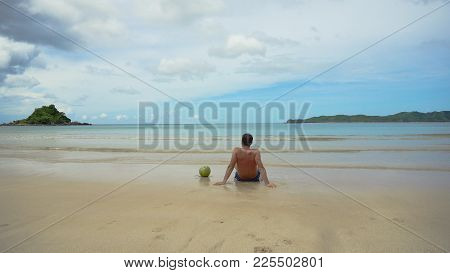 Man Sits On A Sandy Beach And Enjoy The Seascape. Man Relaxing Sitting Down On The Shore Of A White