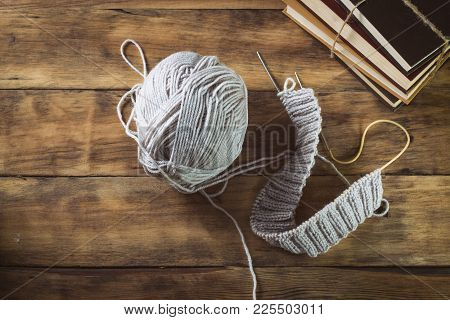 Light Gray Knitting And Knitting Needles, Books On A Wooden Background. Flat Lay, Top View
