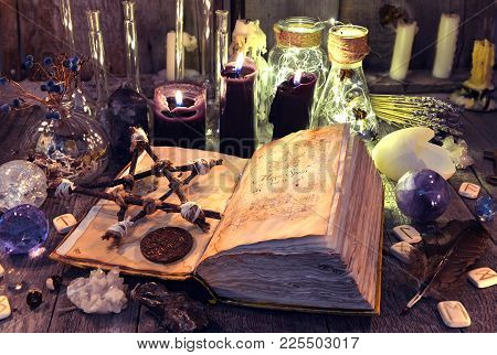 Open Book With Black Magic Spells, Pentagram, Ritual Objects And Candles On Witch Table. Occult, Eso