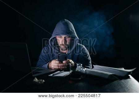 A Male Hacker Sits In A Dark Room And Looks Into The Phone