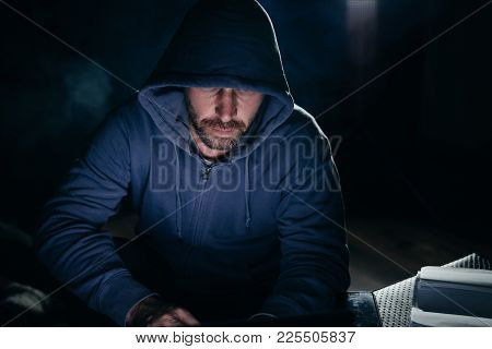 Male Hacker In A Sweatshirt With A Hood Sitting In A Dark Room At The Table