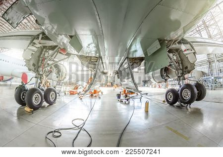 View From Under The Aircraft Between The Chassis Racks Of Wheels In The Hangar