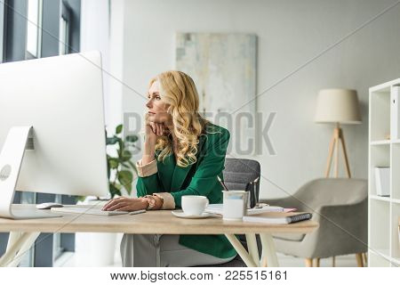 Pensive Businesswoman Looking Away While Using Desktop Computer At Workplace