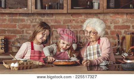 Granny with her lovely granddaughters tasting delicious homemade pie at kitchen
