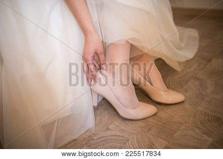 The Bride Touches Her Beige Wedding Shoes. The Bride Is Wearing Her Wedding Shoes. Wedding Day.