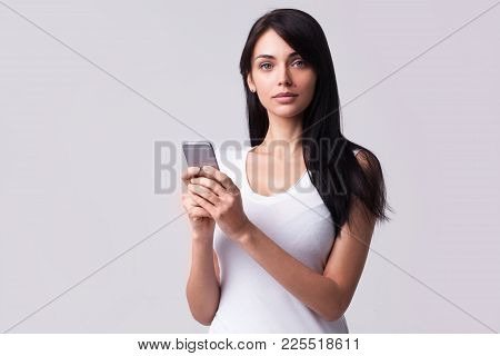 Studio Portrait Of A Young Brunette Woman In Casual Clothes Holding Mobile Phone And Looking Away. I