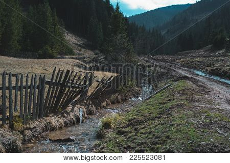Small Brook Against The Old Wooden Fence, In Forest