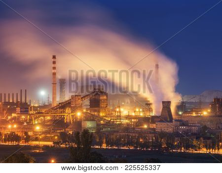 Amusement park with Ferris wheel and buildings on the background of metallurgy plant with smog at sunset. Ecology problems, atmospheric pollutants. Pipes with smoke. Heavy industry factory. Steel mill poster
