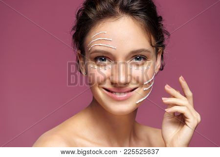Face Lifting. Smiling Girl With Rejuvenating Cream On Her Face On Pink Background. Skin Care And Bea