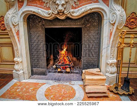 A Classic Style Fireplace With Burning Firewood. A Pile Of Firewood Is Near The Fireplace.