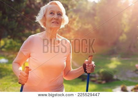 Caring About Health. Waist Up Of Elderly Woman Looking Away While Walking With Crutches And Being Th