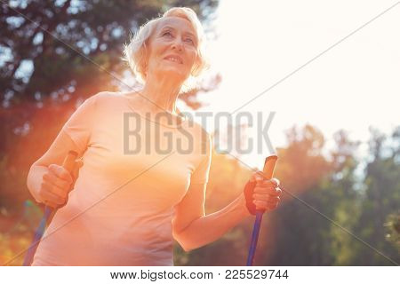 Bright Day. Close Up Of Elderly Woman Having Splendid Mood While Walking With A Help Of Crutches
