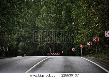 Mountain Road With A Traffic Sign Of Dangerous Turn.