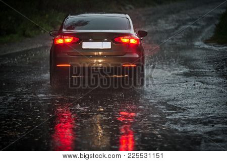 View From A Rain-drenched Windshield On Shower Drenched Back Lights Of A Car In Front. Heavy Rain