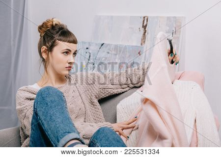 Girl Sitting On Armchair And Skeptically Looking At Sweater On Hanger