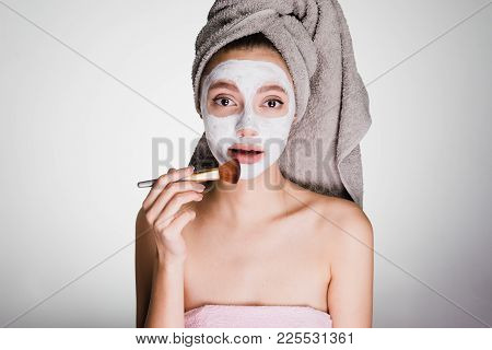 The Amazed Woman With A Towel On Her Head Apply A Cleansing Mask