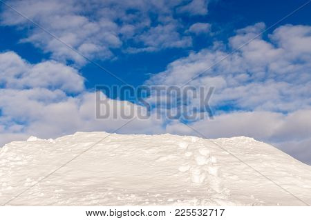 Snowdrift, A Snow Hill With Tracks From A Human, Disappearing Over The Edge. Beautiful Blue Sky And