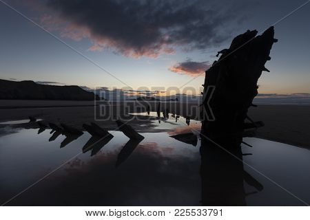 Sunset At Rhossili Bay And Worms Head Showing Remains Of The Ship The Helvetia, A Norwegian Barque,