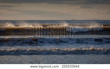 Surf Spray Blowing Off The Top Of Waves At Rhossili Bay On The Gower Peninsula, Swansea, Wales, Uk