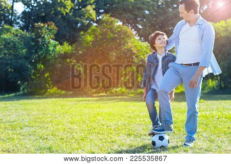 So Proud Of Him. Thoughtful Mature Man Smiling To His Son While Their Legs Standing On A Soccer Ball