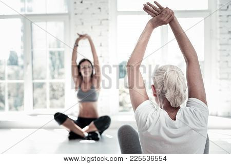 Active Retirement. Selective Focus On A Turned Back Retired Woman Lifting Her Hands And Stretching W