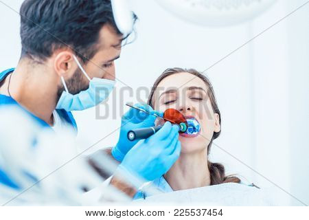 Young woman during innovative oral treatment with cordless LED curing light machine for whitening and restoration in the dental office of an experienced dentist