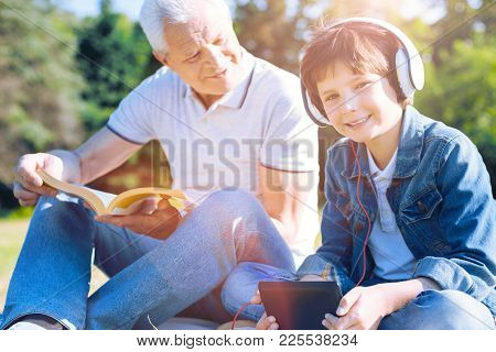 Love My Granddaddy. Selective Focus On A Happy Boy Wearing Headphones Looking Into The Camera With A
