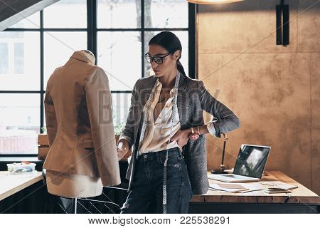 Working On New Order. Serious Young Woman In Eyewear Keeping Hand On Hip And Looking At Mannequin Wh