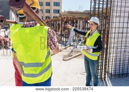Experienced female foreman coordinating and guiding workers by showing them the right direction during work on the construction site of a contemporary building