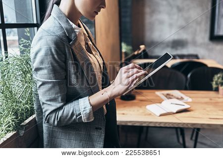 Achieving Best Results. Close Up Of Young Woman In Smart Casual Wear Using Digital Tablet While Stan