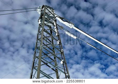 A View Of An Overlooking High Voltage Transmission Tower Under A Blue Sky.