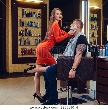 Sexy Female Dressed In A Red Dress Shaving With Straight Razor A Man In A Barber Shop.