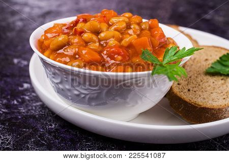 Stewed Beans With Vegetables In Tomato Sauce In A Plate On The Table. Selective Focus.