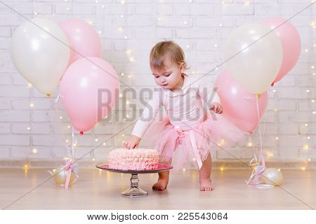 Birthday Celebration - Funny Little Girl Smashing Cake Over Brick Wall Background With Lights And Co