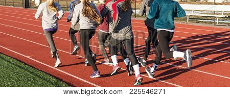 A Group Of High School Girls Running Away From The Camera While Doing A Workout On The Track On A Co