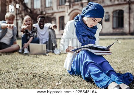 Diligent Student. Nice Pleasant Young Woman Sitting On The Grass And Studying While Preparing For He