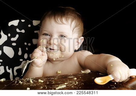 Feeding A Child. Funny Dirty Baby At Meal After Lunch. Close-up Photo On Black Background. Copy Spac