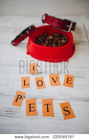 A Bowl Of Dry Dog Food And Red Leather Dog Collar On A White Board Background. Pet Care And Veterina