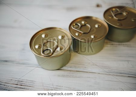 Nutritious Meal For Your Little Buddy. Tin Cans Of Pet Food On A White Board Background. Pet Care An