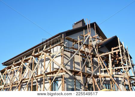 Painting, Stucco And Plastering Unfinished House Scaffolding Facade Wall Exterior.
