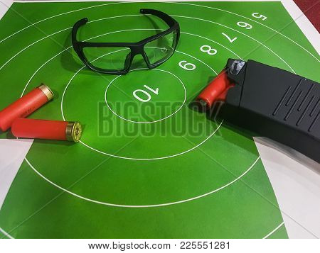 Photo Of Shooting Gallery With Target, Glasses, Gun On Brown Table