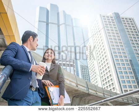 Happy Business colleagues talk outside office & talking to each other. Businessman talk and hold cof