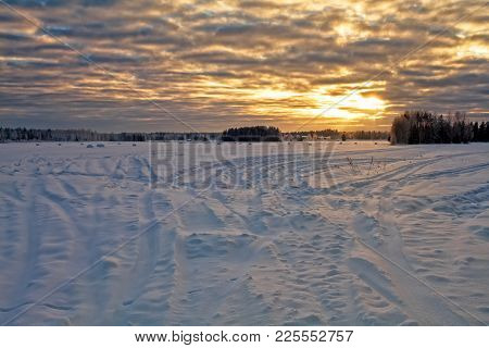 The Sun Sets Over The Snowy Fields On A Very Cold Day In The Northern Finland. The Tractor Tracks Le