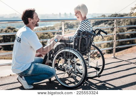 Do Not Worry. Cheerful Positive Optimistic Man Holding An Elderly Womans Hand And Looking At Her Whi