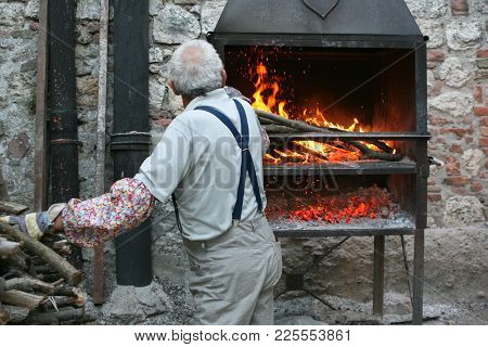 Summer. A Typical Italian Village. Gray-haired Old Man Lights A Fire In The Oven