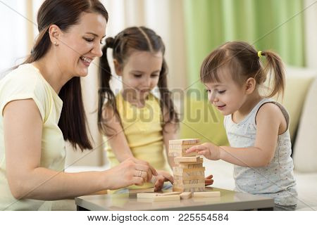 Mother And Her Little Daughters Playing In Board Game