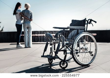 For Disabled People. Selective Focus Of A Wheelchair Standing On The Ground With Nice Positive Peopl